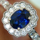 white gold and diamonds around an oval no-heat rich blue sapphire in blossom setting