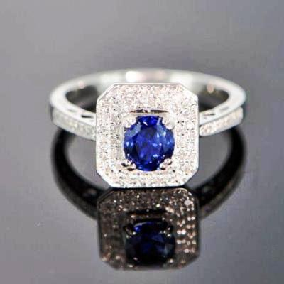 A giant shield of white gold and diamonds around a smaller oval no-heat rich royal blue sapphire in