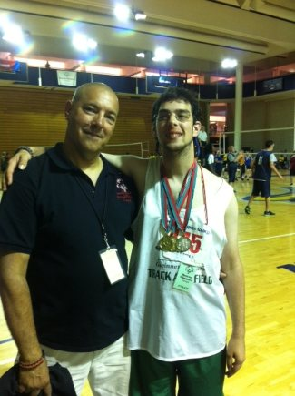 Image description: A white adult male coach is standing with his white athlete son on a volleyball court. The coach is bald, wearing white shorts and a blue polo coach's shirt with a logo on the left breast area. He has an ID tag hanging around his neck on a black lanyard. His son is standing to his left. He has short brown hair, and is wearing wire rimmed glasses, green shorts and a white track uniform shirt. He has 3 medals hanging around his neck on striped ribbons. His right arm is around his dad's shoulders with his right hand resting on his dad's left shoulder. They are both smiling at the camera.